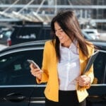 Cheerful young businesswoman in yellow jacket holding folder and using cell phone outdoors